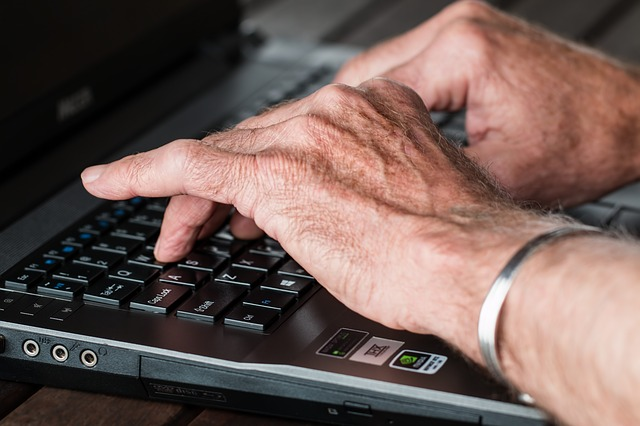 man with arthritis typing on computer
