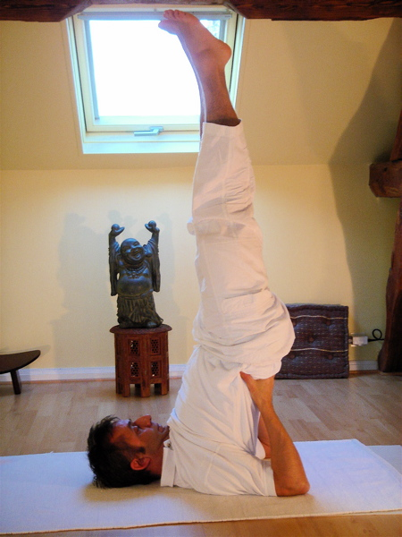 man doing a should stand yoga pose